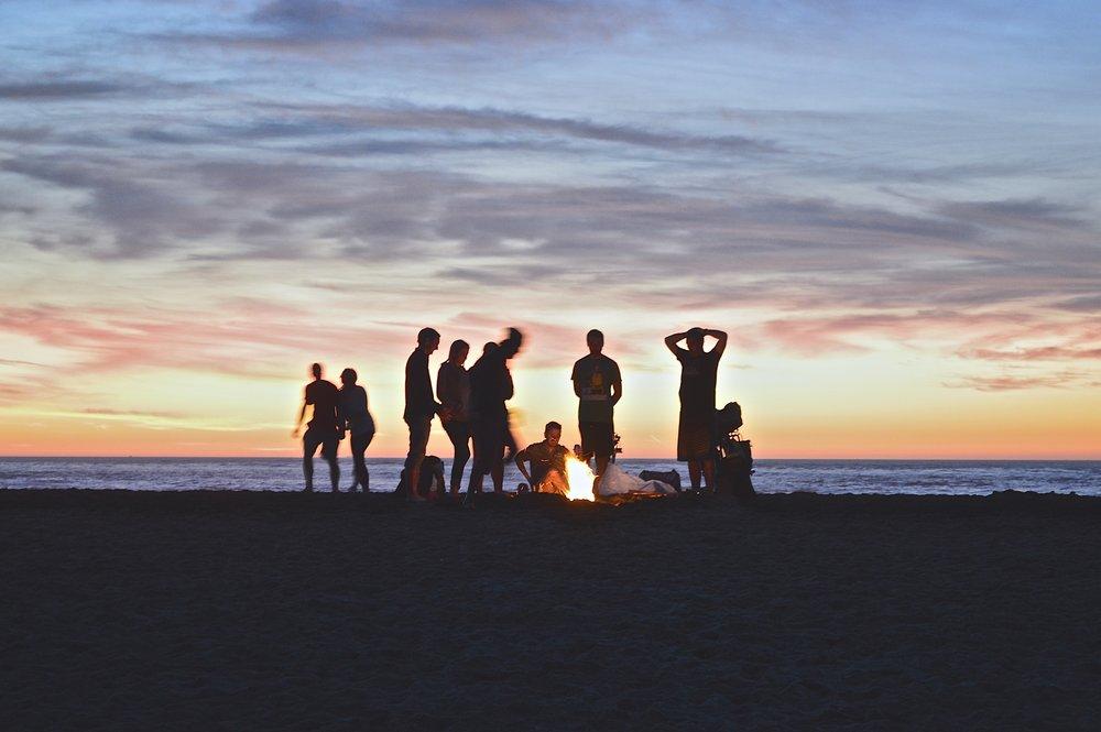 Unge mennesker hygger sig rundt om et bål på en strand